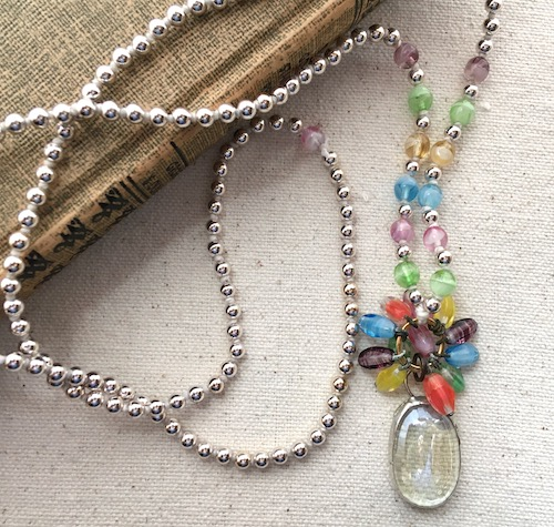 Long knotted necklace with a clear glass and silver soldered pendant, various colors of glass beads and silver beads.