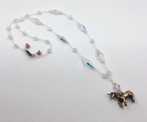 Necklace with clear AB coated crystals with spaced knotting on waded linen and a bronze unicorn pendant.