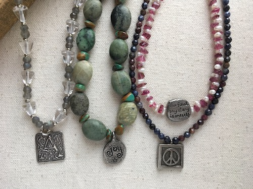 Same four necklaces in previous pictures turned over to show the back of the pendants.