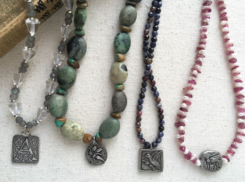 Four small gemstone necklaces with small silver and pewter pendants.