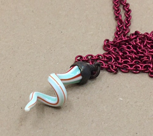 A third photo of the swirly lampwork glass drop necklace on different paper.