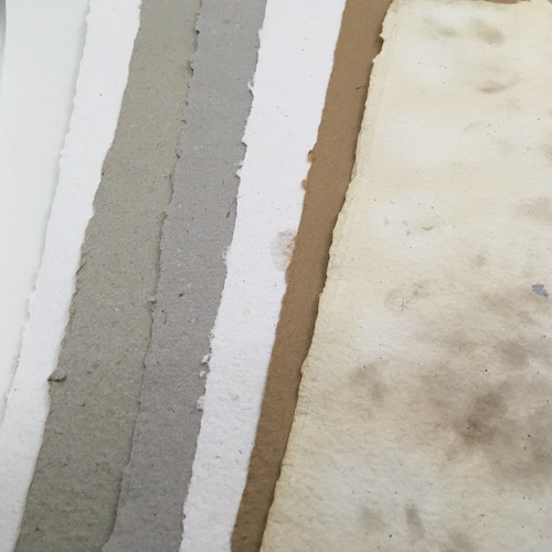 Several handmade papers in various neutral colors - whites, greys, and browns.