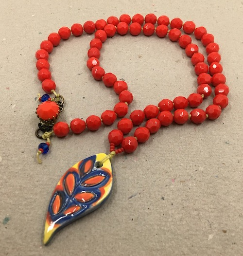 Red, yellow and blue primary color leaf shaped pendant with lipstick red glass beads knotted on linen with a red box clasp.