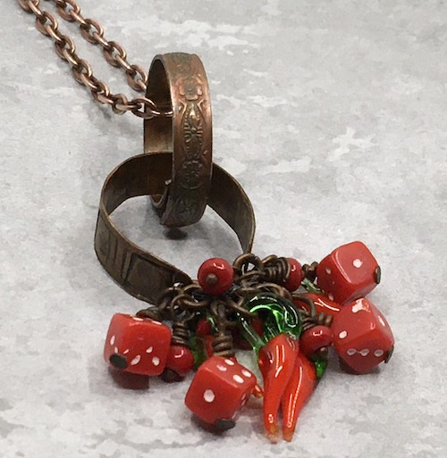 Textured metal rings and red glass elements form the pendant for a necklace on copper chain.