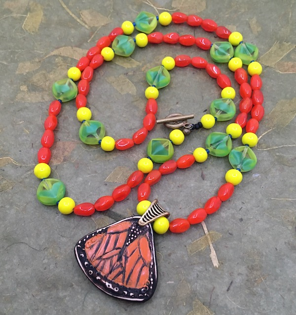 Necklace with monarch butterfly pendant and bring rice shaped orange, round yellow and diamond table cute green beads inspired by the above photo.