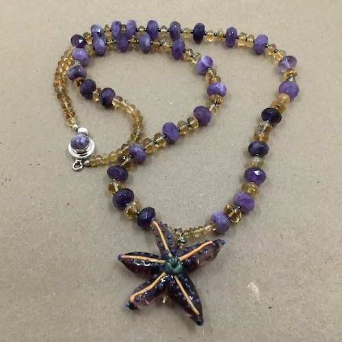 Purple and light orange lampwork starfish pendant with alternating citrine and amethyst beads and a silver and amethyst clasp.