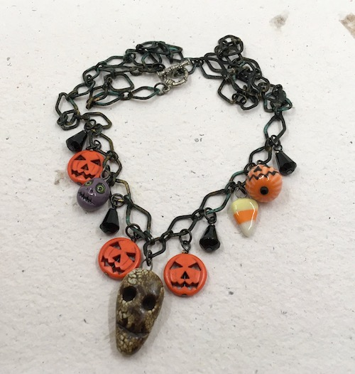 Aged black patina on diamond shaped metal chain with jack-o-lantern, ghoul, candy corn and jet back drop beads. Larger grungy skull pendant in front.