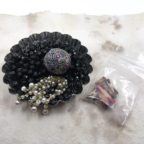 Materials pulled together for a potential design - black glass beads, patterned large polymer focal bead and pearl tassel in a dish. Rolled, painted wood bark beads in a baggie.