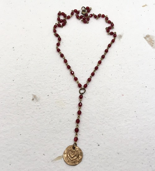 Photo of Y shaped necklace of rosary chain with Andrew Thornton circle heart metal pendant. Photo background is handmade paper, white with floral petals embedded.