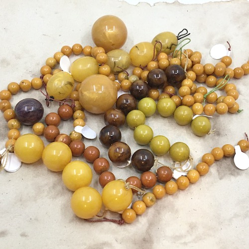 Variety of sizes and colors of round and oval bakelite plastic beads - mostly browns and yellows