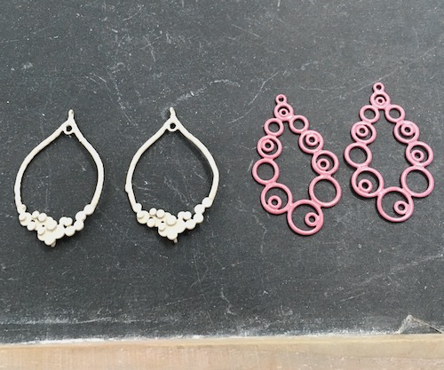 Two metal earring forms, one white loops with bubble decorations at the bottom, one pink with swirly circle all around.