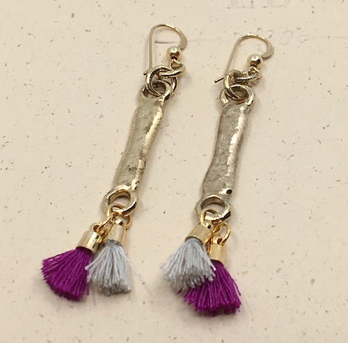Earrings made from gold organic shaped stick connectors with two small tassels at the bottom of each - one grey and one purple.