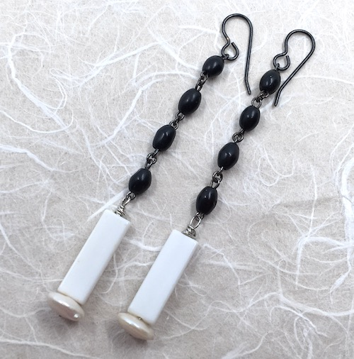 Earrings with black wooden beaded chain sections, white glass rectangles and white disc pearls.