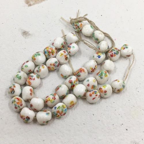 Organic shaped roundish white glass beads with millefiori type colorful splotches.
