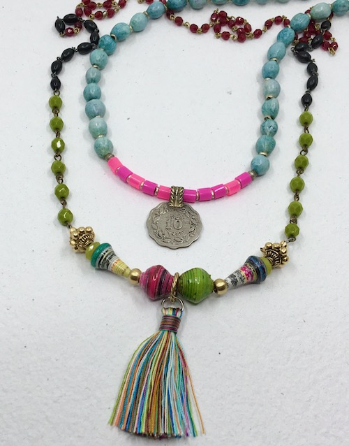 Two colorful, layered necklaced. Longer one with paper beads, gold plated metal, multi-color tassel and rosary chain in green, black and red. Shorter necklace with silver coin medallion, bright pink and fuchsia Perler beads, old silver metal spacers and turquoise dyed Job's tears seeds.