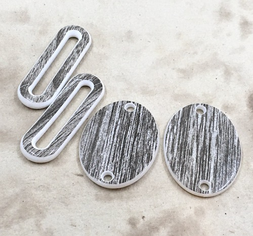 Two sets of plastic connectors, white and dark brown. One set is elongated ovals with open middles. One set is flat ovals with holes at either ends.