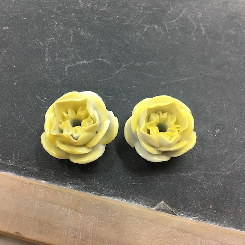 Yellow porcelain flowers with holes in the metal and many petals.
