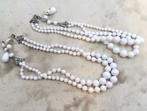 Double strand knotted necklaces of graduated white beads.