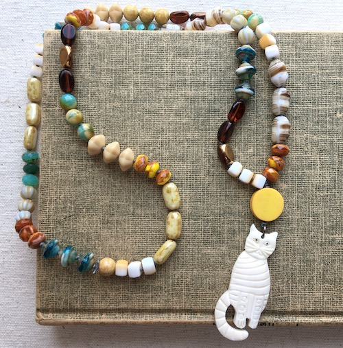 Necklace laying on book. Necklace has off white carved cat bead, with yellow coin bead above it and a variety of cream and brown glass beads in different shapes accented by a few blue tone beads.