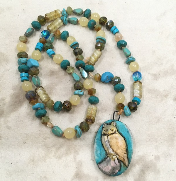Necklace featuring an oval pendant with a turquoise background and a tan owl on a branch. The strand has a variety of shapes, sizes and shades of mostly glass beads in tans and turquoise. The background is brown/tan mottled handmade paper.