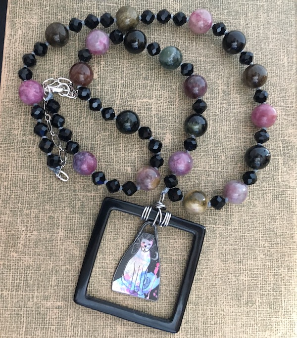 Tan textured background with necklace featuring pendant of black open square with a multi-colored cat charm inside and multi-colored tourmaline round beads with smaller black beads in between.