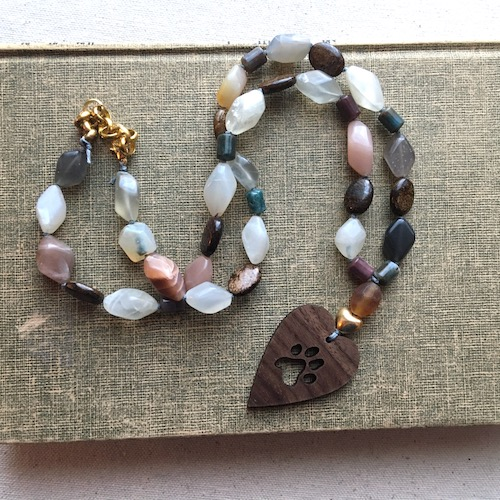 Necklace with wooden pendant showing a paw print cut out and diamond shaped and ovals gemstone beads in brown, white, peach and grey colors.