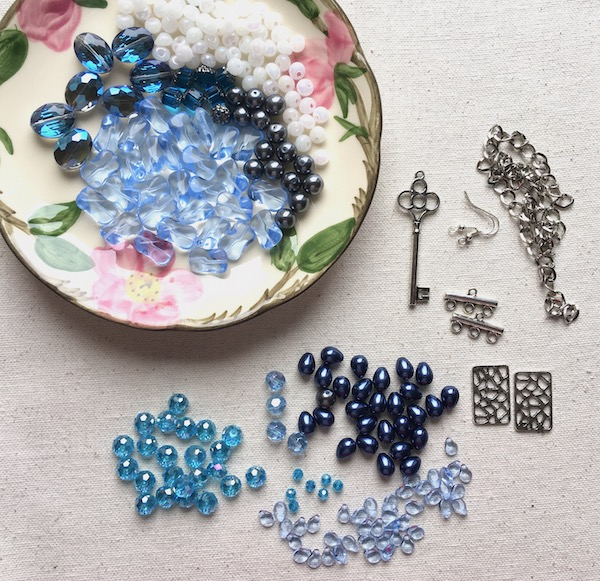 Materials for this blog hop including a variety of blue beads, white beads and silver metal findings.