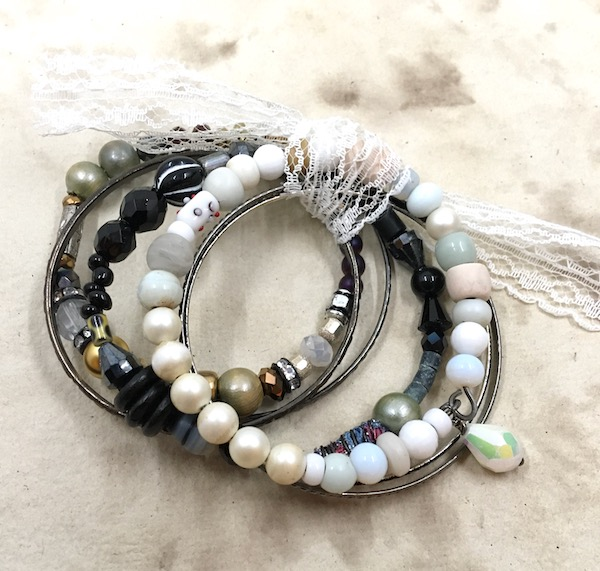 Stack of three beaded bangle bracelets with various beads, one primarily white, one primarily black and one featuring metallics and sparkle, tied together with a lace ribbon.
