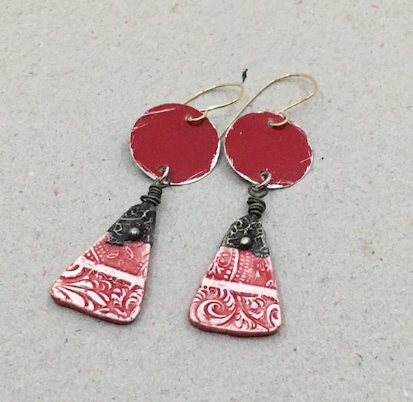 Earrings consisting of red tin circles and red and white textured ceramic triangles with stamped tin work at the top.