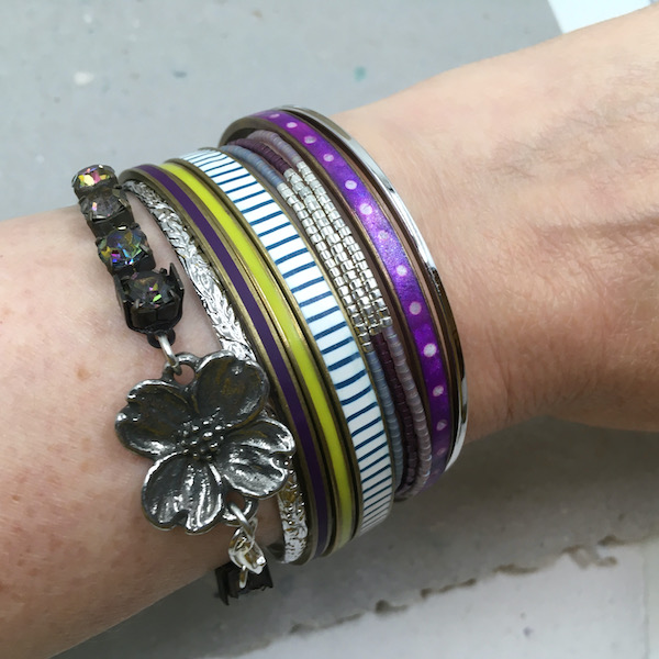 Bracelet stack shown on an arm with purples and silvers being the dominant colors with a little blue and green.