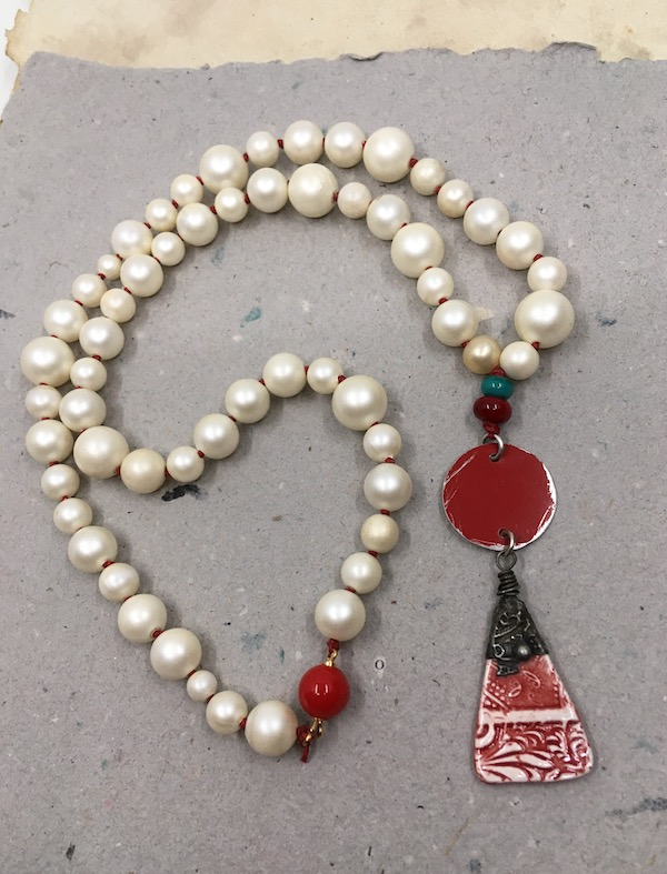 Necklace made with one of the earrings from the picture above (red tin circle and red and white ceramic triangle with stamped tin work on top) knotted with two small lampwork beads - red and teal - and semi-matte off white pearls on red linen with a round red clasp.