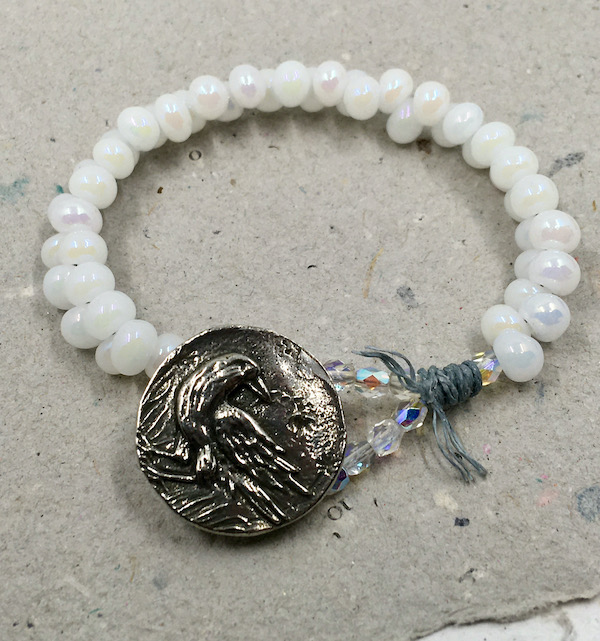 Bracelet made of white beads with AB coating, crystals, fiber and pewter button with a crow design.