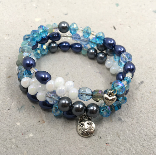 Triple wrap memory wire bracelet with a variety of all of the beads from the kit above, along with one silver cat charm and one silver heart charm.