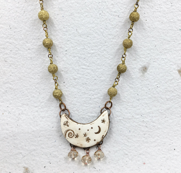 Same necklace as above hanging on textured handmade paper.
