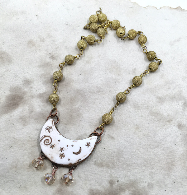 Mottled brown paper with necklace on it. Necklace has beaded chain with sparkly brass beads, white curved half moon pendant with starts, moons, swirls and dots and three faceted crystals hanging from the bottom.