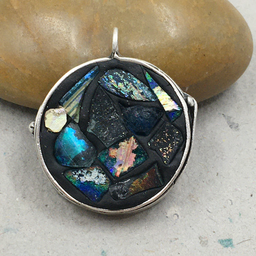 Silver bezel pendant leaning against a rock filled with black clay with variously shaped shards of Roman glass with old, rough patina in some shiny blue, black, grey and metallic colors.