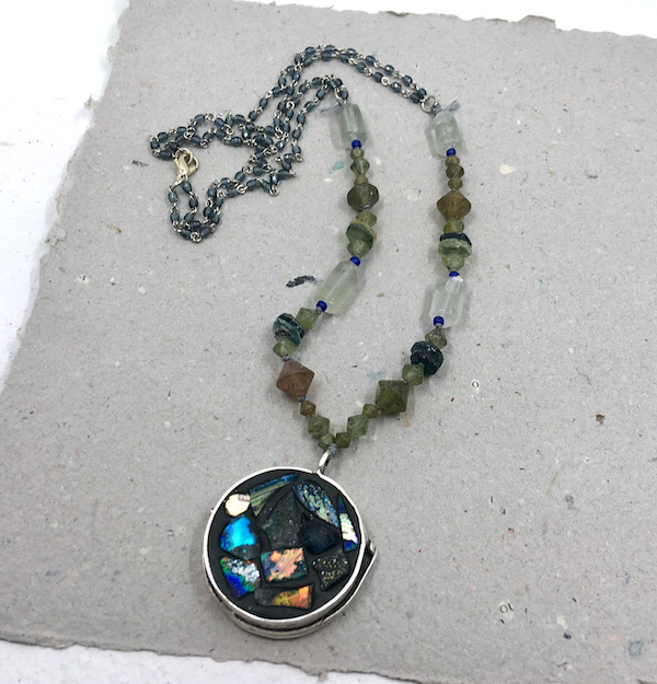Pendant from above with a strand made up of Roman glass beads in various shapes with small blue beaded chain in the back.