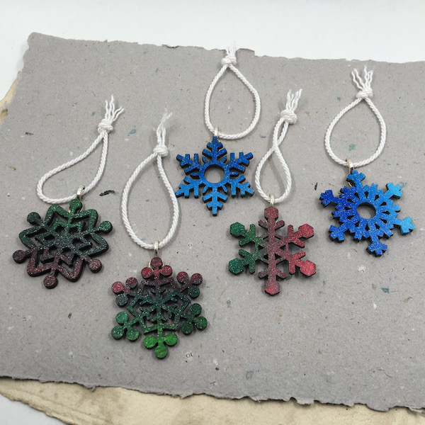 Wooden snowflakes in different shapes - some blue some red and green, all with glitter and white rope hangers.