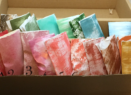 Hand painted coin envelopes in different colors and patterns nestled together in a cardboard box. Each has a black number stamped in the corner.