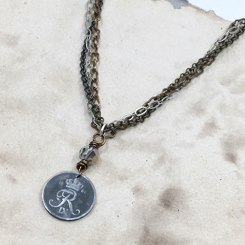 Necklace of an old Danish coin wire wrapped with a crystal above it hanging on three strands of different metal and different designs of chain on a brown and tan mottled paper background.