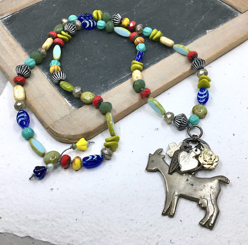 Necklace of an aged silver billy goat milagro with smaller mixed metal milagros above it (most visibly a silver heart and a gold rose) on a necklace of mixed color, shape and pattern glass beads on a background of handmade white paper and a vintage wooden framed child's writing slate.