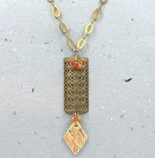 Necklace of open metal work brass rectangle with orange and yellow ceramic botanical diamond pendant hanging off the bottom with three orange bead dangles. More orange bead dangles are at the top where the metal work pendant connects with oval brass chain. This is on a background of grey handmade paper.