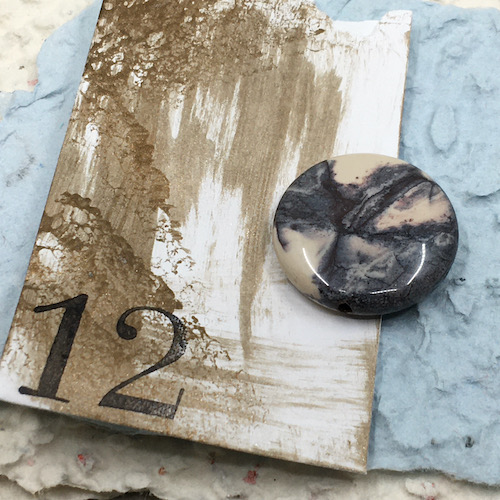Cream and grey coin shaped stone bead on handmade grey/blue paper and hand painted coin envelop in gold with a black number 12 stamped in the corner.