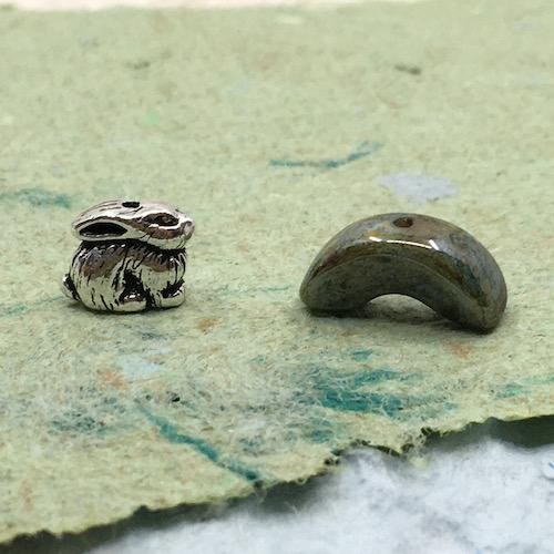 Tiny silver bunny charm and green half round ceramic bead on green handmade paper.