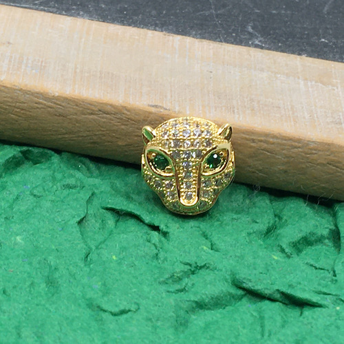 Gold metal leopard bead with white rhinestone face and green rhinestone eyes on green handmade paper leaning against the wooden side of a vintage writing slate.