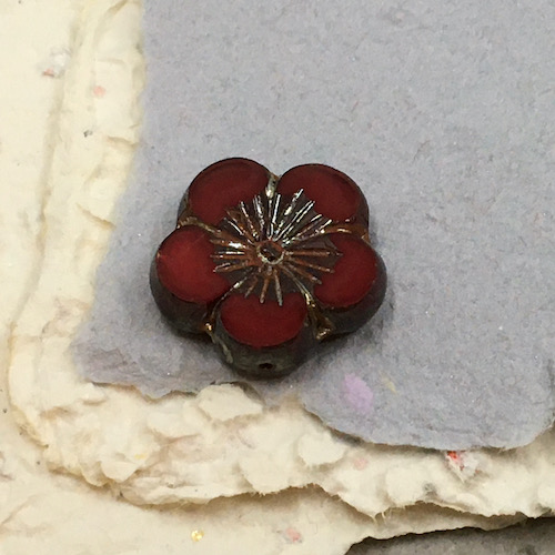 Large dark red glass flower bead with brown/silver details in the middle on stacked pieces of handmade paper in grey and cream.