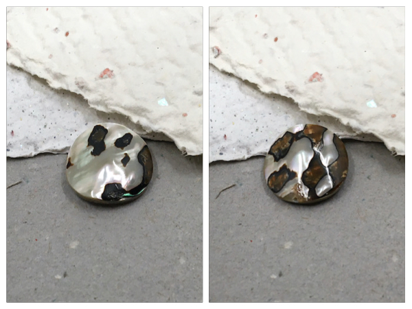 Two photos side by side of the front and back of a mother of pearl bead sitting on grey and white handmade papers.