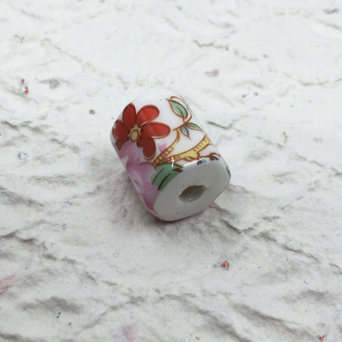 Thick white faceted barrel bead with red and pink floral decal with green leaves and tan branches features on white diamond textured handmade paper with bits of glitter.