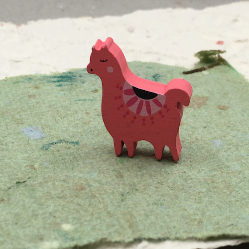 Salmon colored wooden lama bead with painted details on green handmade paper with cream handmade paper underneath.