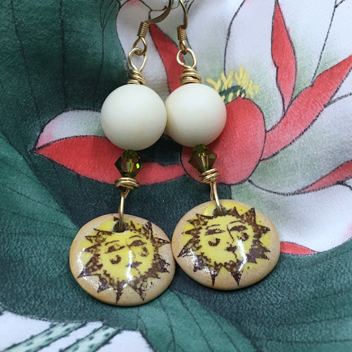 Earrings on a floral fabric bagkround Earrings have large off-white beads, small green crystals and yellow and brown sunshine charms.